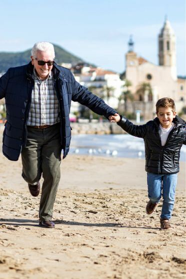 Grandpa and grandson during at the beach during our day trip to Tarragona and Sitges