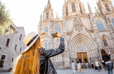 Woman taking a picture of the Cathedral near the hotels in Barri Gotic