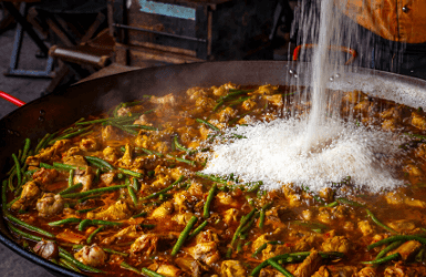 Adding rice to paella in a Barcelona restaurant