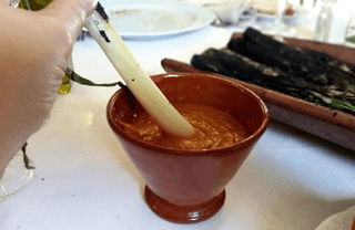 Dipping a Catalan Spring onion on sauce