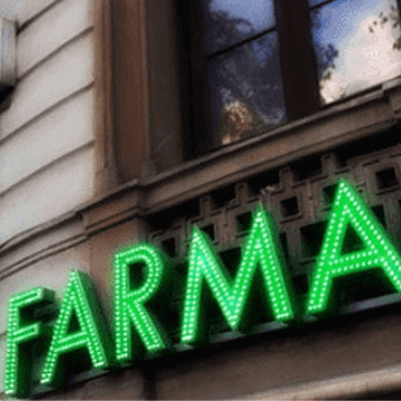 Green FARMA letters from a Barcelona pharmacy sign