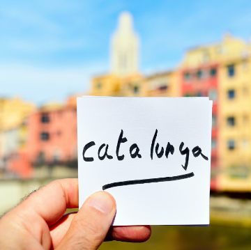 Post-it with the word Catalonia, with Girona in the background, one of the favorite Barcelona Day Excursions   ForeverBarcelona