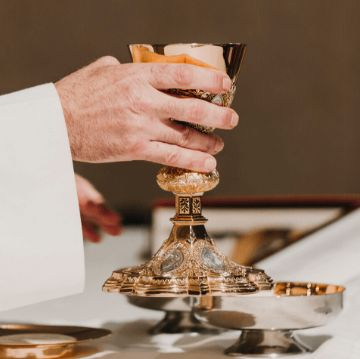 Hands of a priest holding a goblet during Christmas mass in Barcelona