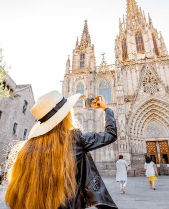 Lady taking a picture of the Cathedral during her half day tour in Barcelona