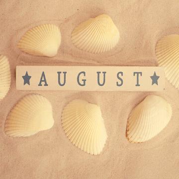 "Word ""August"" written in a piece of wood in a Barcelona beach"
